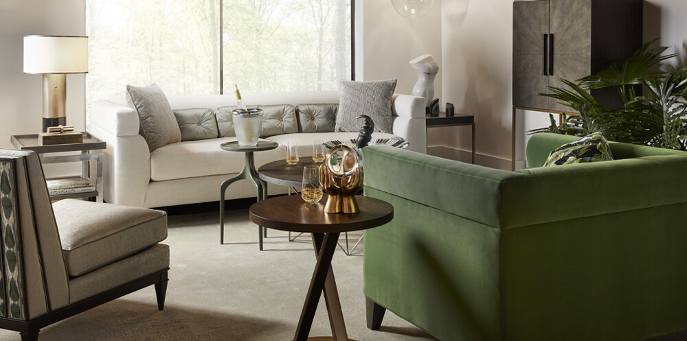 green interior design trend picturing a neutral living room with large window and light coloured sofa opposite a dark green armchair