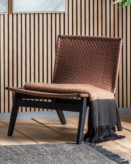 a brown leather woven armless Japandi chair with black wooden legs