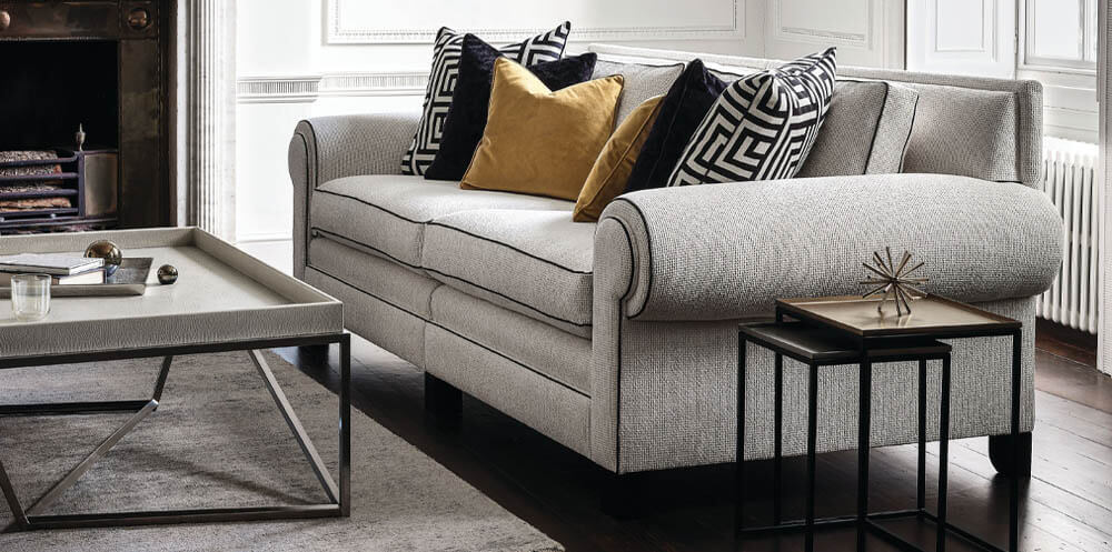 monochrome interior design trend featuring a large silver coloured sofa decorated with gold and black and white scatter cushions