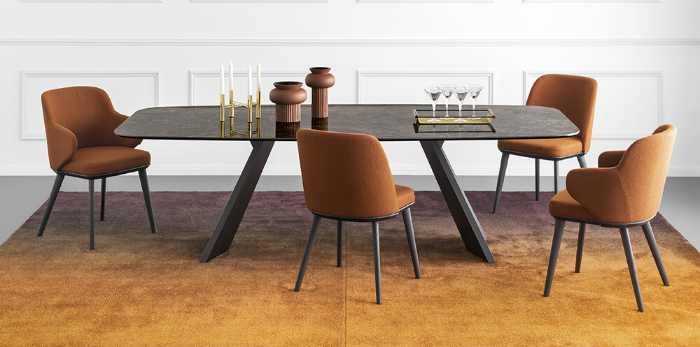 orange interior design trend picturing a long dining table with 4 orange upholstered chairs and a ombre orange rug
