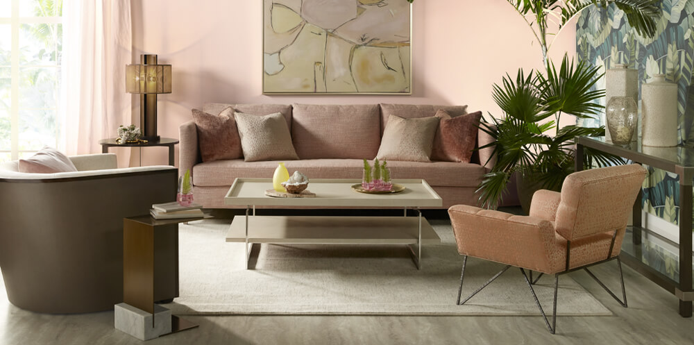 pink interior design trend featuring a light pink sofa and chair in a light and spacious living room with pink wall