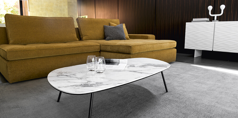 yellow interior design trend featuring a yellow modular sofa in a modern living room with white coffee table