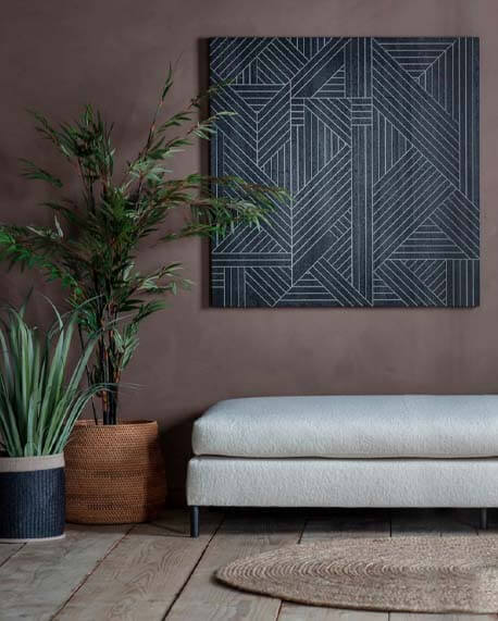 Black geometric wall art piece in a neutral room with bare wooden floors and natural textures
